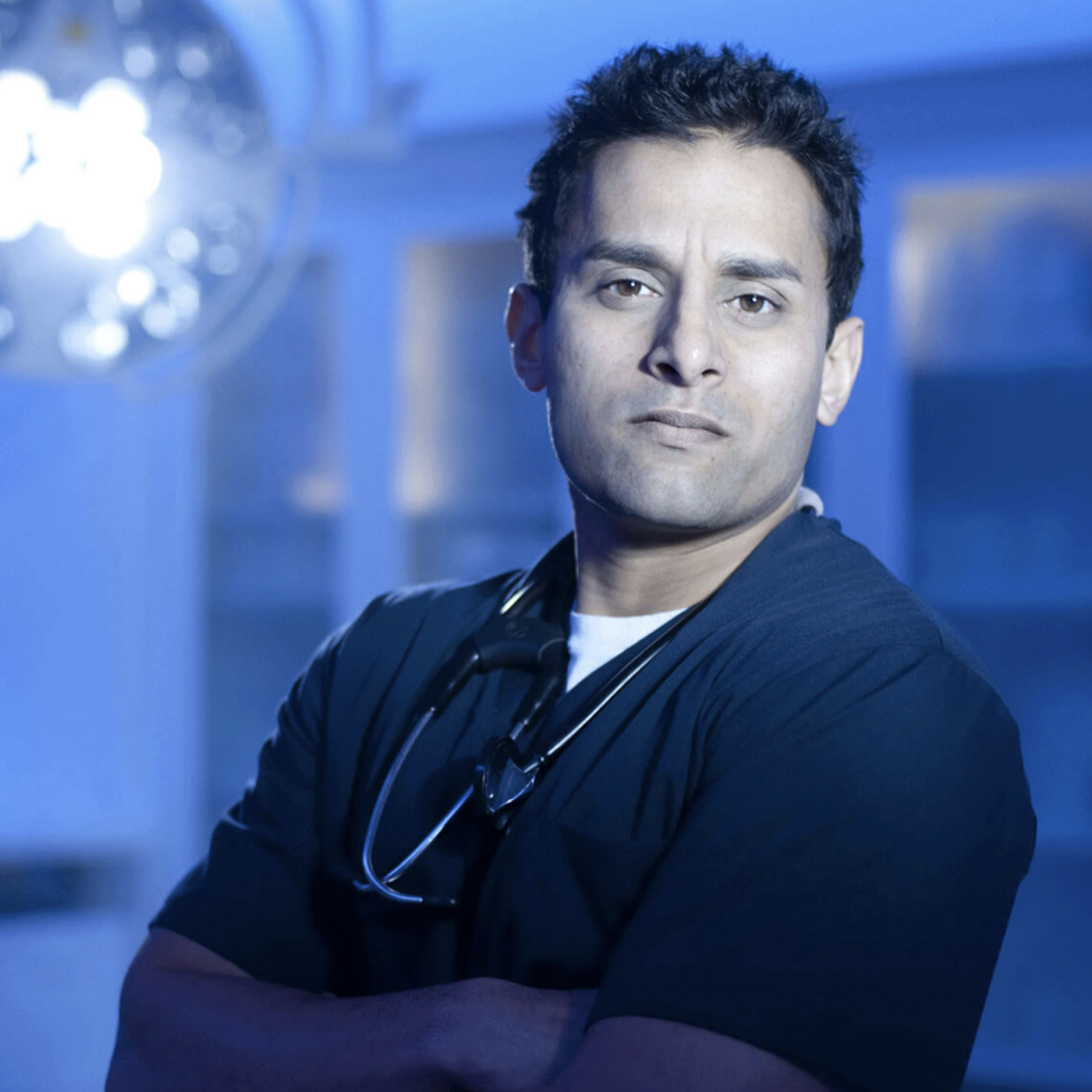 Dr. Sudip Bose standing in surgical theater wearing dark blue scrubs and stethoscope around his neck.